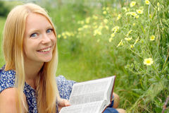 Woman Reading Bible Outside. A young attractive woman laying in the grass outside, reading the book, the Bible stock images