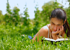 Woman reading a book. Young attractive woman reading a book lying on a grass Royalty Free Stock Photography