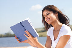 Woman reading book. Young beautiful happy arabic woman reading on beach Royalty Free Stock Photos