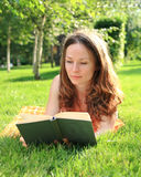 Woman reading book. Young smiling woman reading in summer park royalty free stock photography