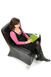 Woman reading a book. A woman sitting on a chair is reading a book Royalty Free Stock Photos