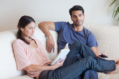 Woman reading a book. While her boyfriend is watching television in their living room Stock Photos