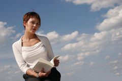Woman reading a book. With the blue sky filled with clouds in background Royalty Free Stock Image