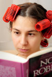 Woman reading a book. Young woman with hair rollers to read a book Stock Photo