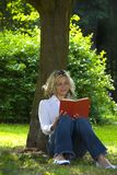 Woman reading book. Young woman relaxed and reading a book in the park Royalty Free Stock Image