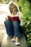 Woman reading book. Modern young woman reading book in park in old color style Stock Photos