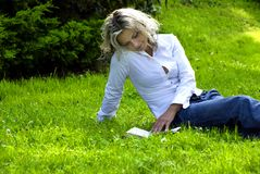 Woman reading book. Young modern woman reading book in grass Royalty Free Stock Photos
