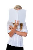 Woman reading a book. A young woman is reading a white book Stock Images
