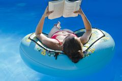 Woman reading book in airbed at swimmingpool Stock Photo