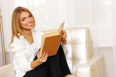 Woman reading a book in the armchair Stock Photo