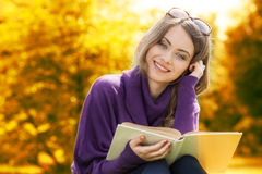 Woman reading book in autumn scenery Stock Photo