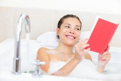 Woman reading book in bath Stock Photography