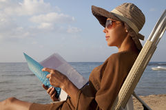 Woman reading book at beach. And sitting in lawn chair Royalty Free Stock Photos