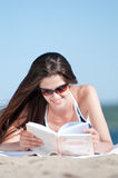 Woman reading a book on the Beach. Close up of a beautiful young woman reading book on beach Stock Photography
