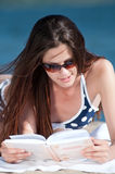 Woman reading a book on the Beach. Close up of a beautiful young woman reading book on beach Stock Images