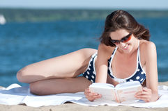 Woman reading a book on the Beach. Close up of a beautiful young woman reading book on beach Royalty Free Stock Photography