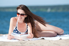 Woman reading a book on the Beach Stock Images