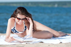 Woman reading a book on the Beach. Close up of a beautiful young woman reading book on beach Stock Photo