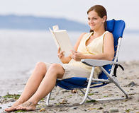 Woman reading book at beach. Woman reading book at the beach Royalty Free Stock Photo