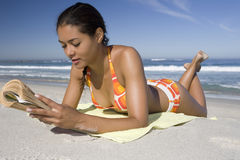 Woman While Reading Book At Beach Stock Images