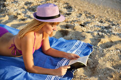 Young woman reading a book on the beach. Attractive young woman reading a book on the beach with a hat Royalty Free Stock Images