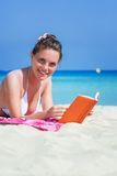 Woman is reading a book on a beach Royalty Free Stock Photo