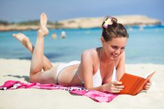 Woman is reading a book on a beach Stock Photography