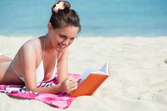 Woman is reading a book on a beach Royalty Free Stock Images