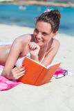 Woman is reading a book on a beach. Pretty brunette woman is reading a book while lying on a beach Royalty Free Stock Images