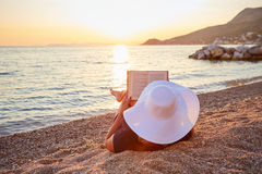 Woman reading a book on the beach. At sunset Stock Photos
