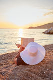 Woman reading a book on the beach. At sunset Royalty Free Stock Images
