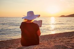 Woman reading a book on the beach. At sunset Stock Photo