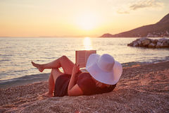 Woman reading a book on the beach at sunset. Young woman reading a book on the beach at sunset Royalty Free Stock Photo