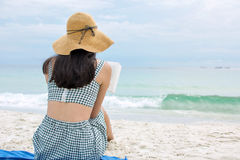 Woman reading a book on the beach. Young woman reading a book on the beach Stock Photography