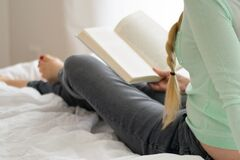 Woman reading book in bed Stock Image