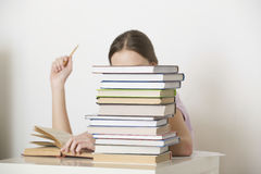 Woman Reading Book Behind Stack Of Books Stock Image