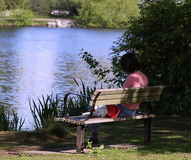 Woman reading book on bench. Woman enjoying the sun and solitude while reading a book Royalty Free Stock Images