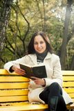 Woman reading book on bench. In park Royalty Free Stock Image