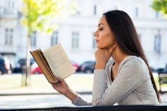 Woman reading book on the bench outdoors Stock Images