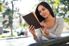 Woman reading book on the bench outdoors Stock Photography