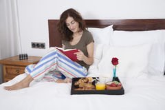 Woman reading book at breakfast Royalty Free Stock Image