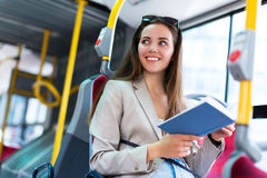 Woman reading book on bus stock images