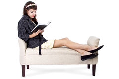 Woman Reading a Book on a Chaise Lounge. Retro girl sitting on chaise lounge reading a book on a white background royalty free stock photos
