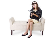 Woman Reading a Book on a Chaise Lounge Stock Photo