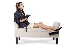 Woman Reading a Book on a Chaise Lounge. Retro girl sitting on chaise lounge reading a book on a white background stock images
