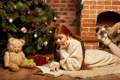 Woman reading book on Christmas in front of tree royalty free stock image