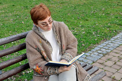 Woman reading a book in the city park Royalty Free Stock Photo