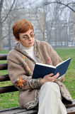 Woman reading a book in the city park Stock Image