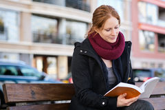 Woman Reading a Book in a City Stock Photo