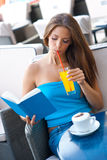 Woman reading book in coffee shop Royalty Free Stock Photo